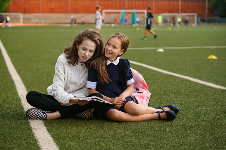 Girls reading a book while sitting on a football field