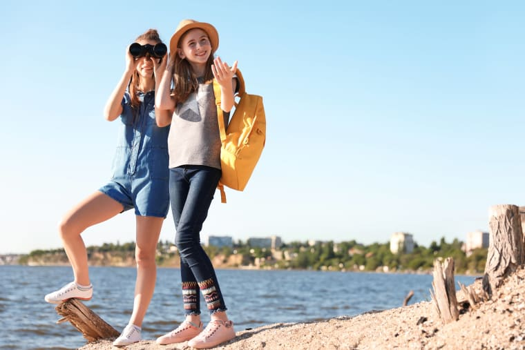 Two girls on the seashore standing while one is looking through binoculars