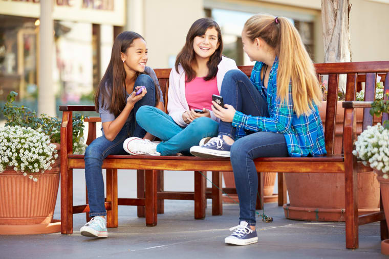 Girls sitting on a bench and talking