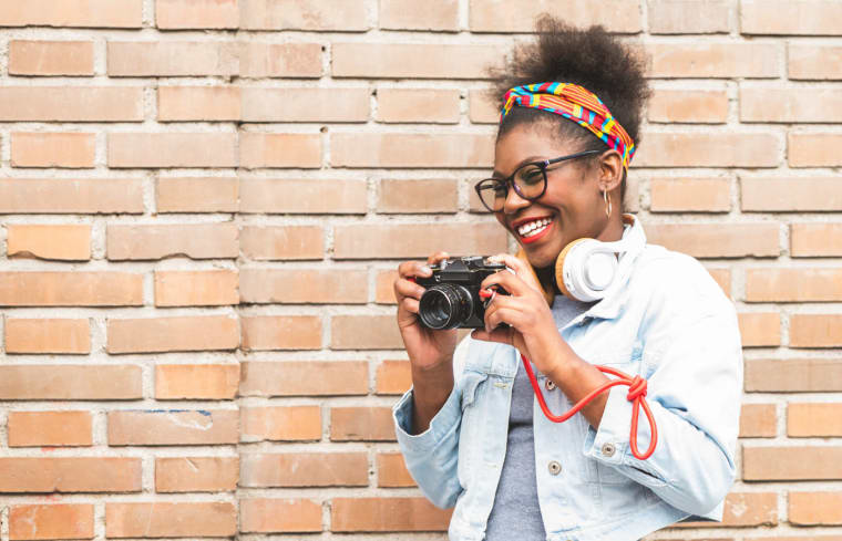 Woman in front of a brick wall smiling and holding a camera