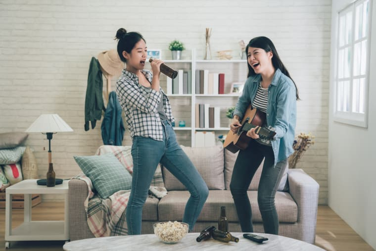 Two girls singing and playing a guitar in the living room