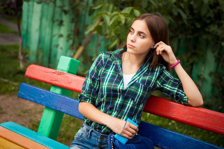 Girl sitting on a bench and looking at the distance