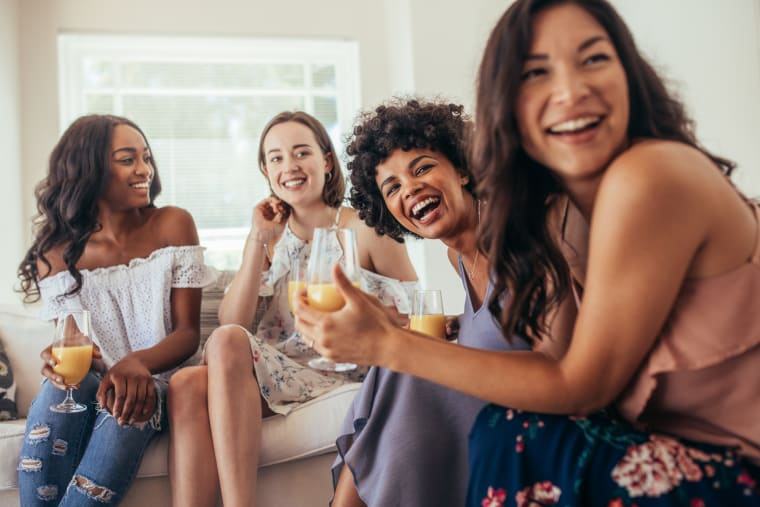 Four women having drinks and smiling