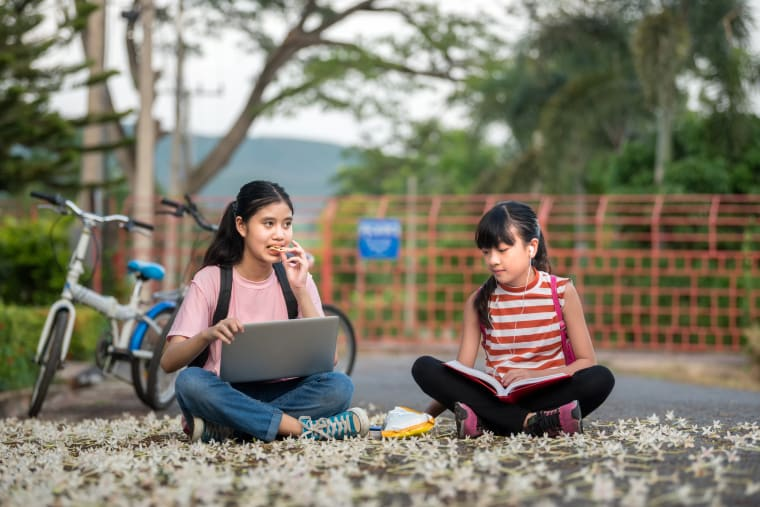 Two girls sitting on the ground outside