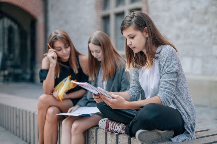 Girls sitting outside and reading