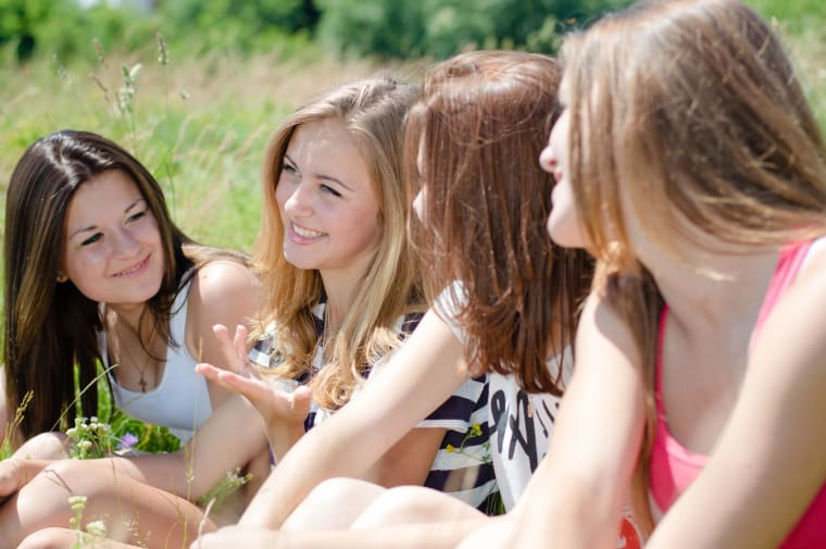Girls sitting in a field and smiling