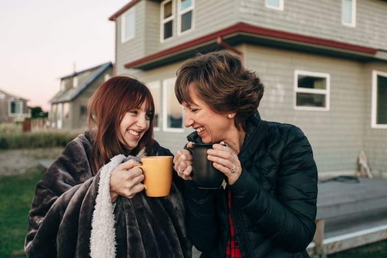 Daughter and mother drinking tea outside and smiling
