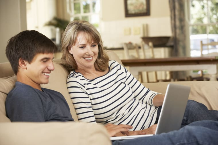 Son and a mother sitting at a couch and looking at a laptop screen