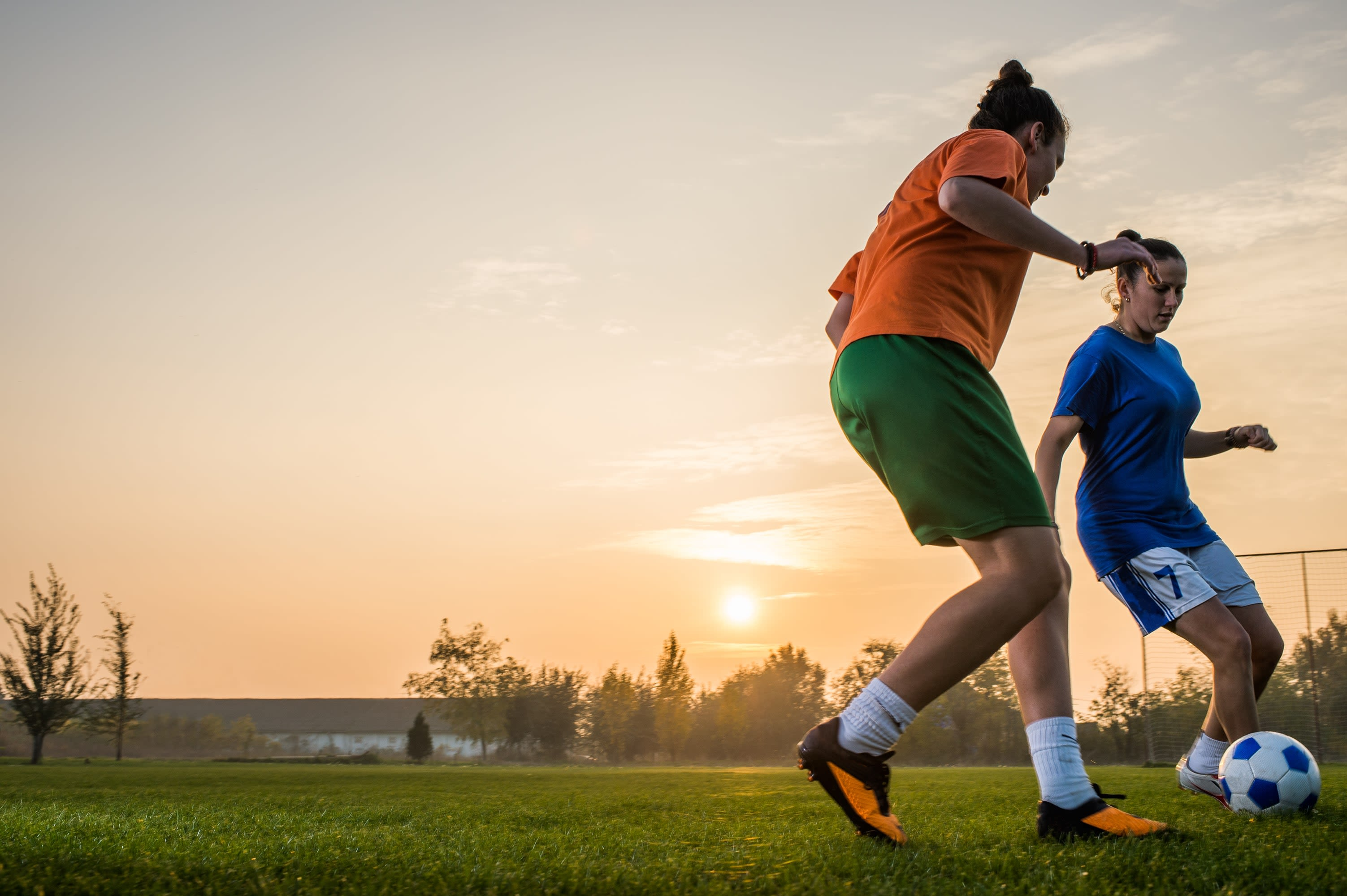 Two women playing football in the sunset