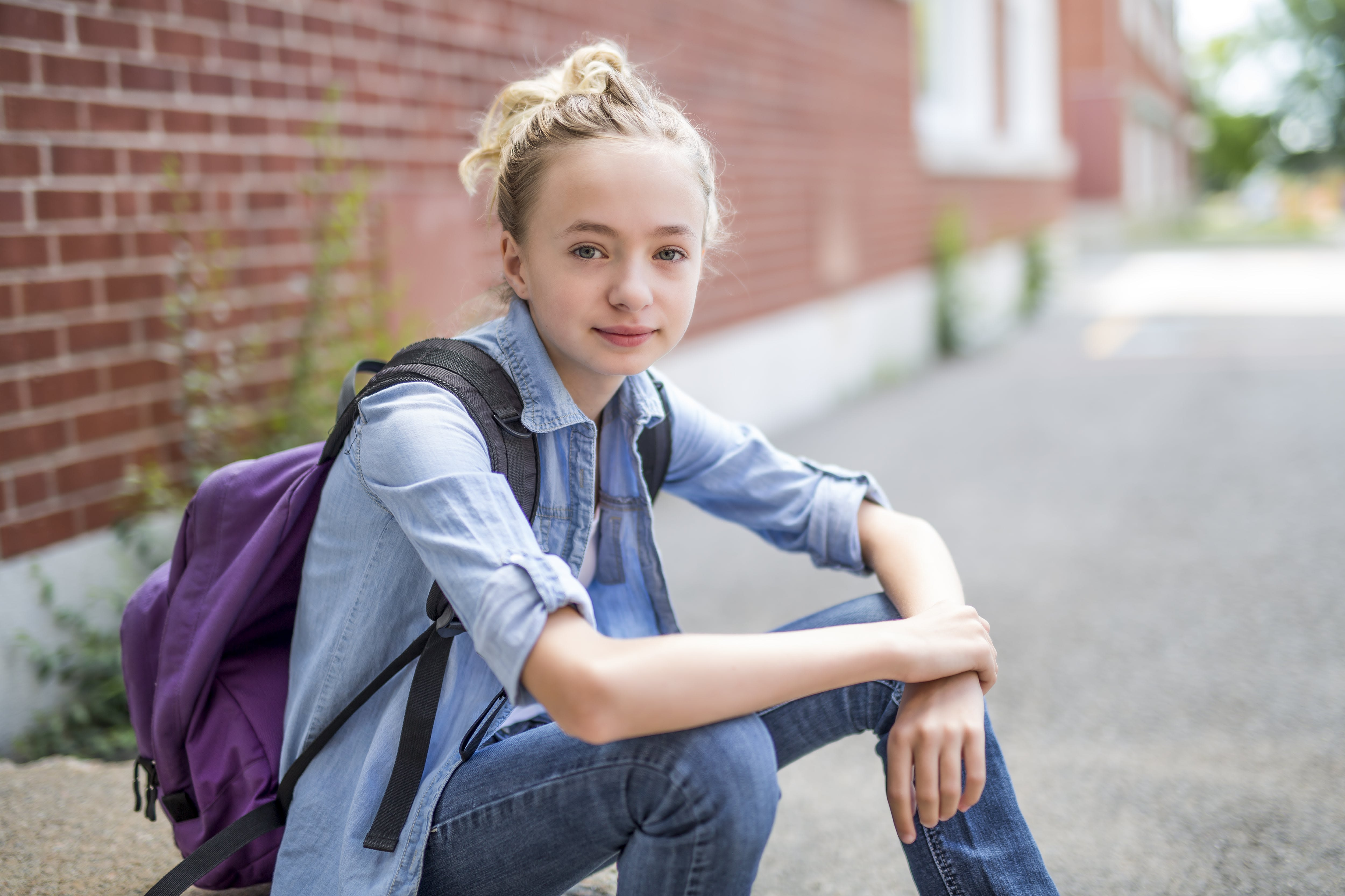 Girl sitting in front of a brick wall