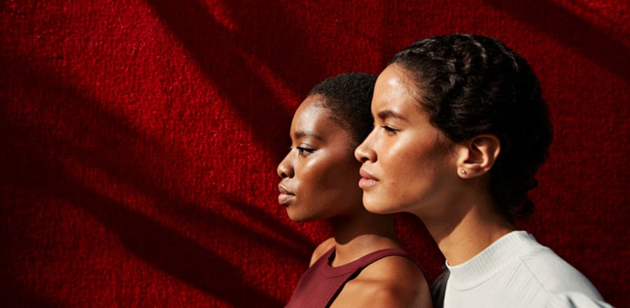 Two afro girls soaking up the sun in front of a red wall