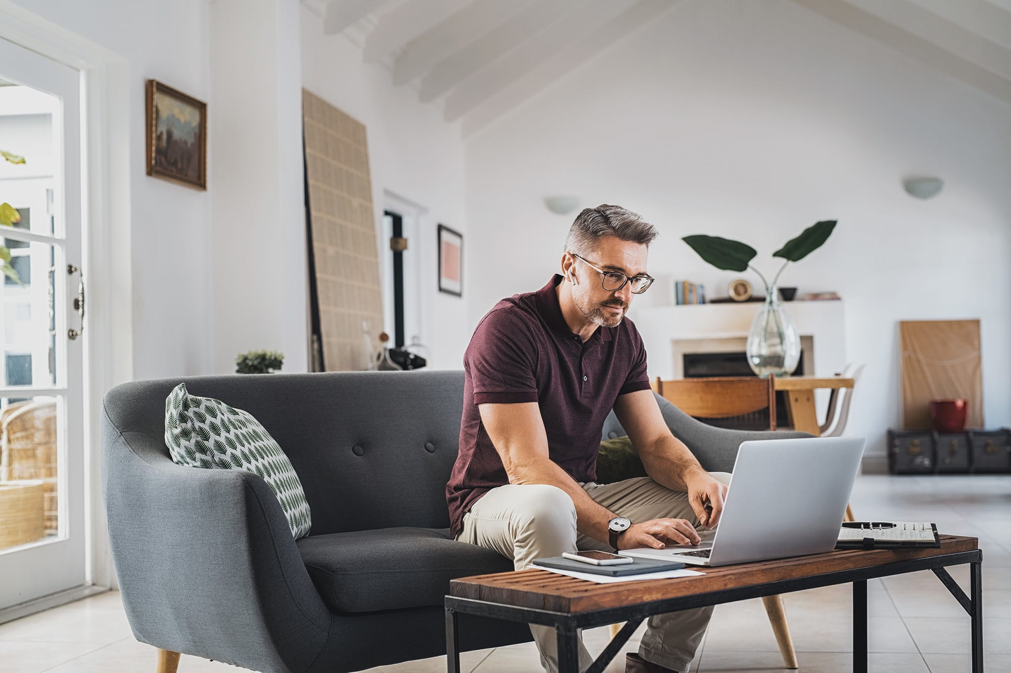 Man sitting on sofa at home working on laptop.