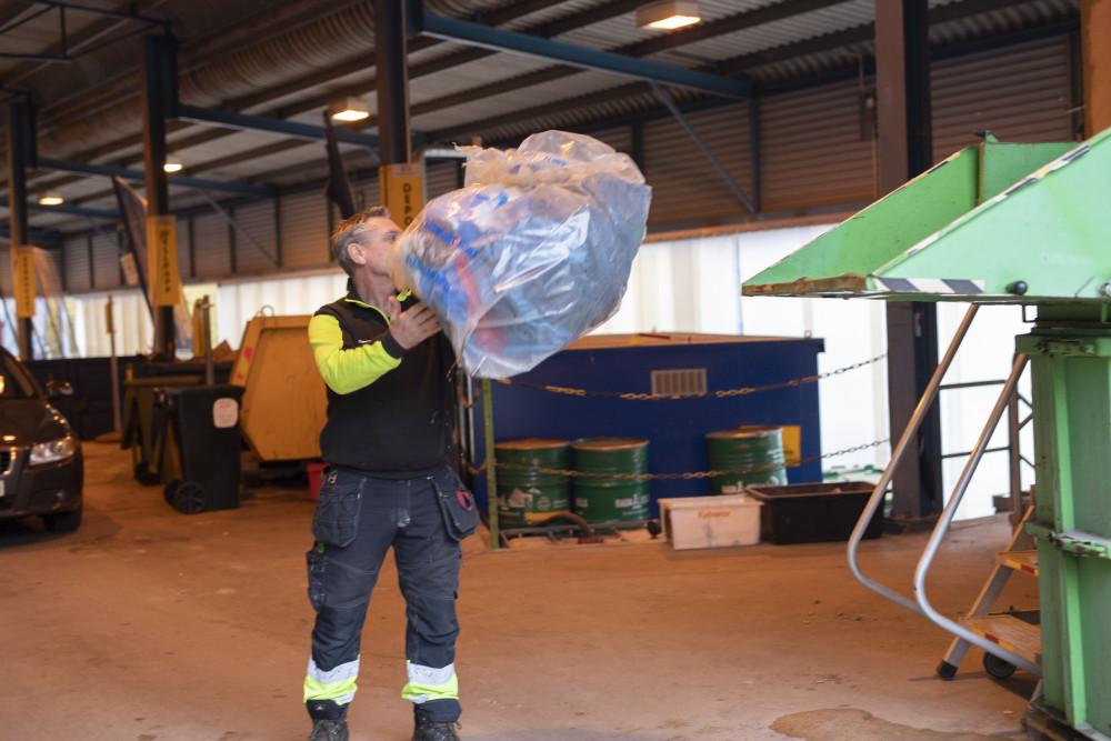 Conny Månsson slänger utsorterad mjukplast i en komprimator på återvinningscentralen i Tollarp