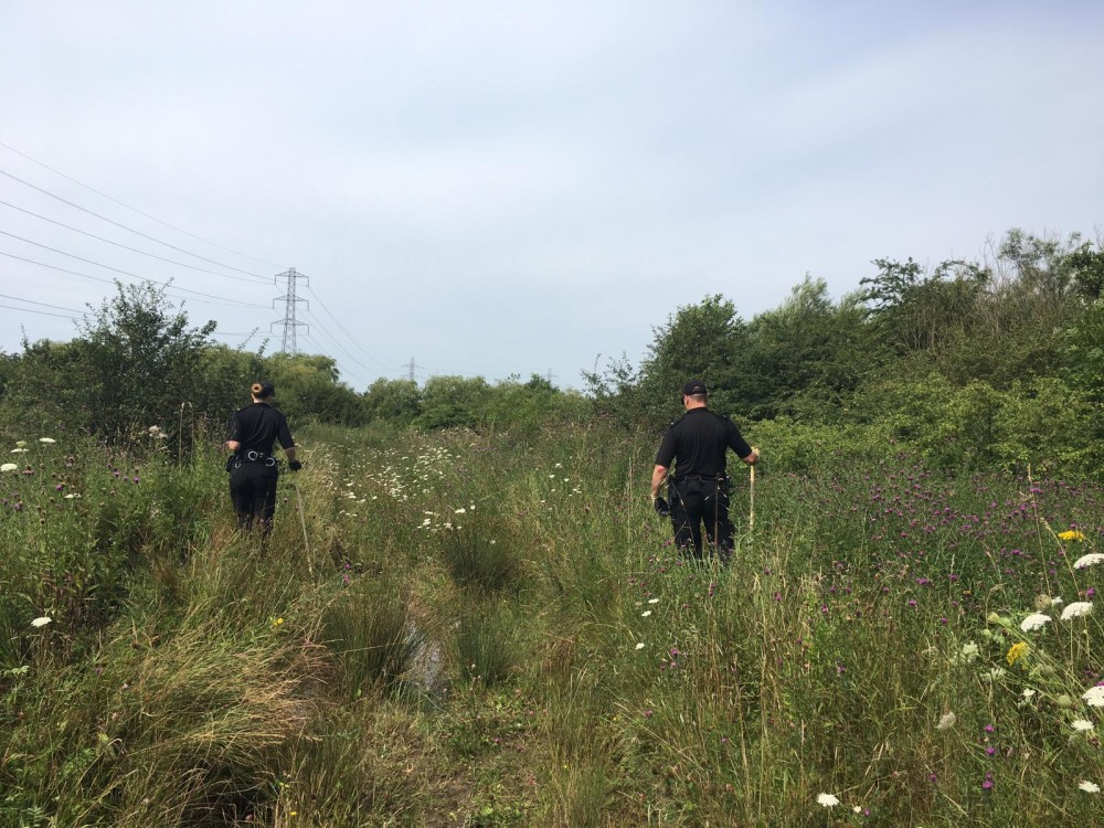 Officers search land near Spencers Lane and the Leeds Liverpool canal