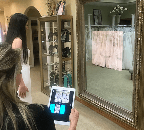 Bride looking at photos on the Magic Mirror the bridal shop attendant has selected on the iPad app.