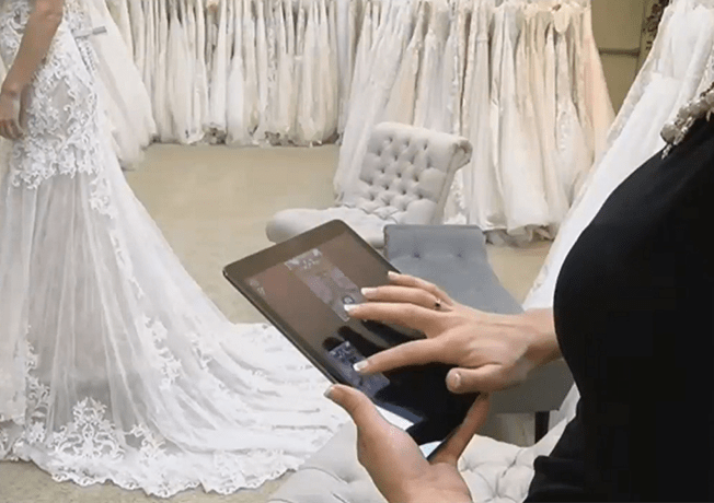 Bridal shop attendant interacting with magic mirror ipad app.