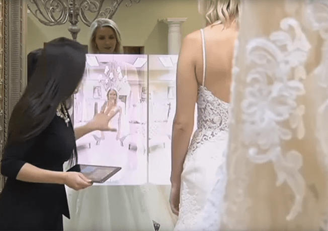 Bridal shop attendant showing soon to be bride photos on Magic Mirror.