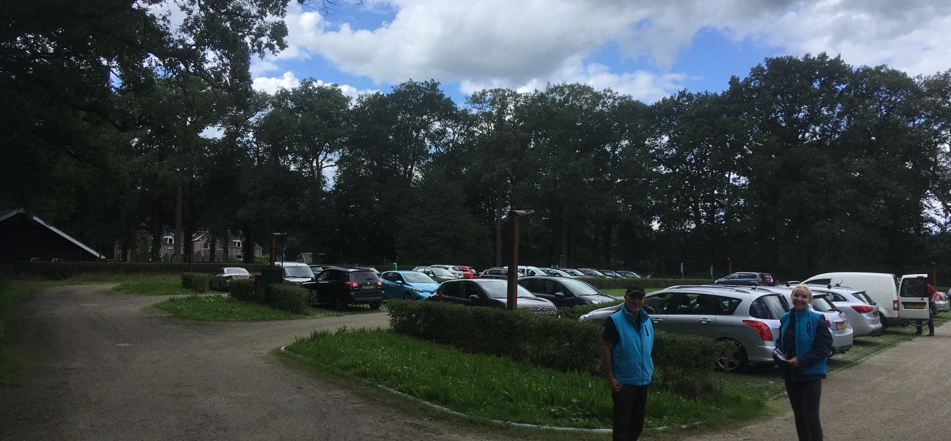 Gastheren ne -vrouwen heten bezoekers welkom op de parkeerplaats op drukke momenten