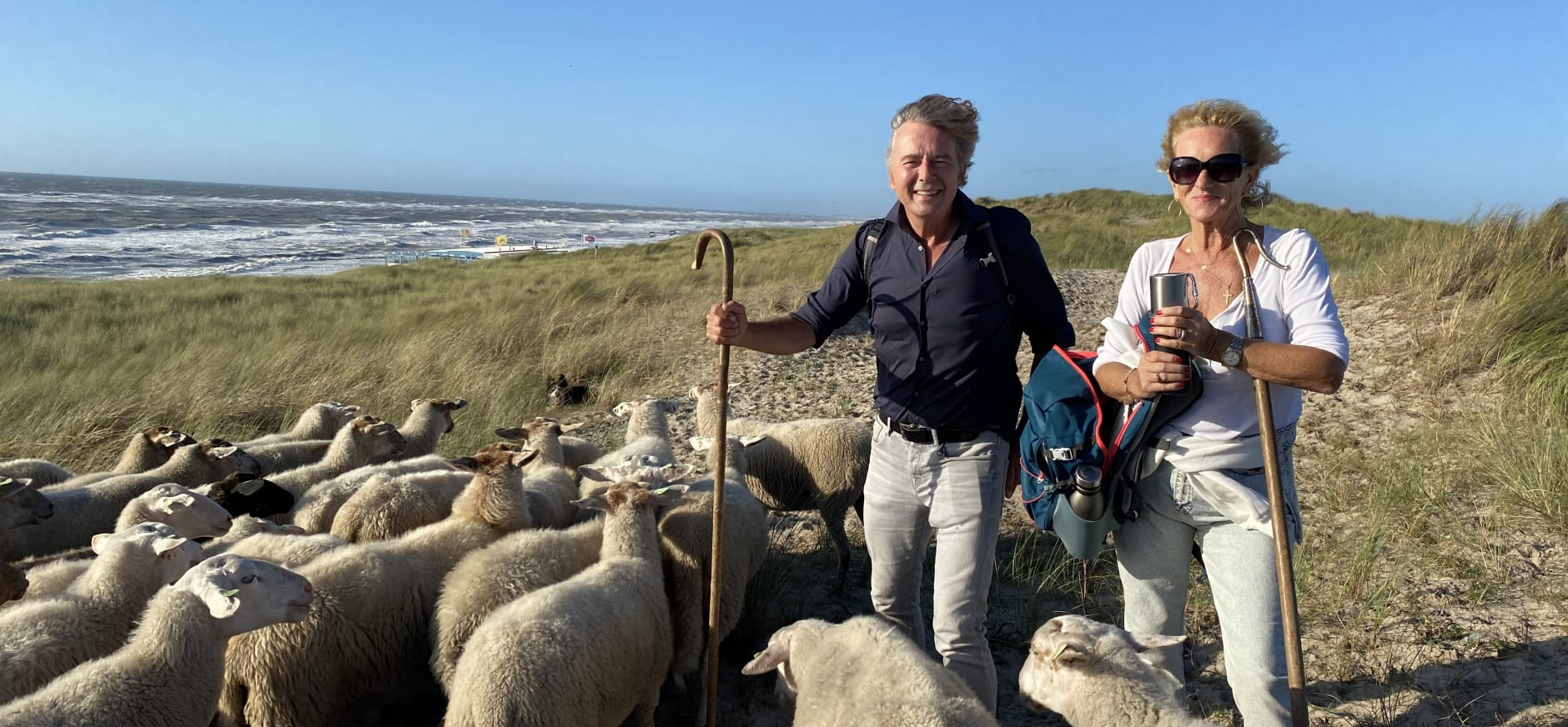 Tineke Schouten en Bert van Leeuwen tussen de schaapjes met uitzicht over zee