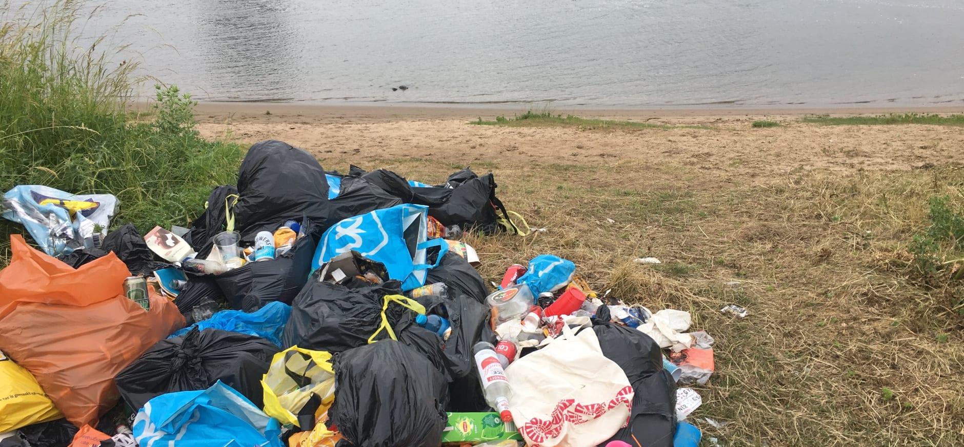 Afval op de oever van de Maas