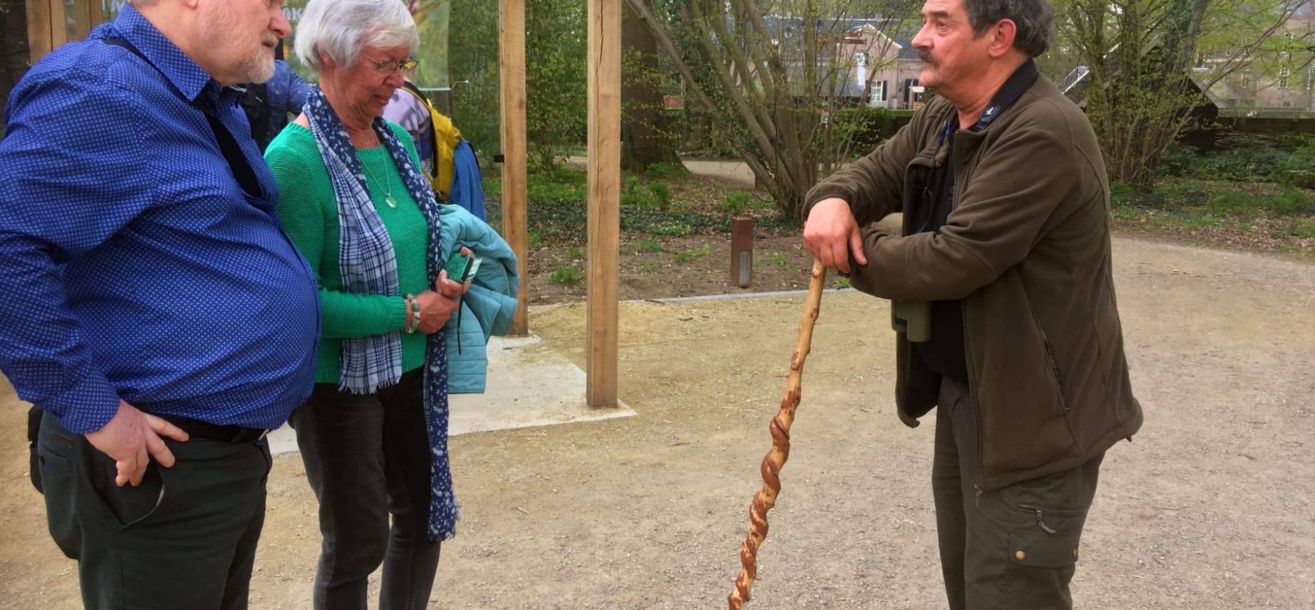 Boswachter Ronald met zijn kenmerkende stok in gesprek met bezoekers