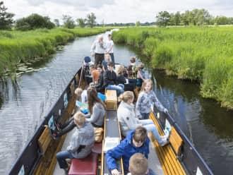 Een boot vol leerlingen tijdens het lesprogramma van De Wieden