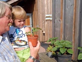 Grootouder met kind bij boerderijwinkel