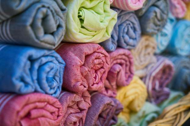 32. A textile factory uses 5 yards of fabric to make a dress. How many dresses can be made with 255 yards of fabric?