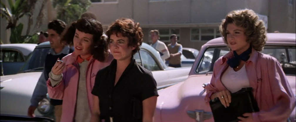 14. After Danny is rude to Sandy to look cool in front of his friends, how does Frenchy cheer her up?