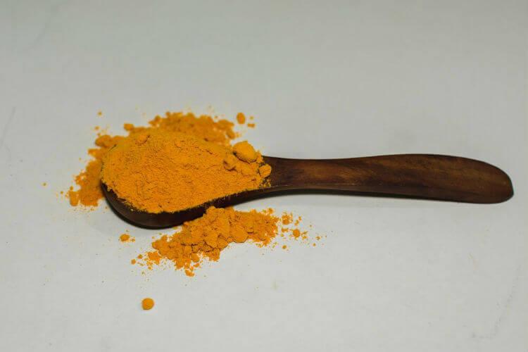 Wooden spoon with orange turmeric powder