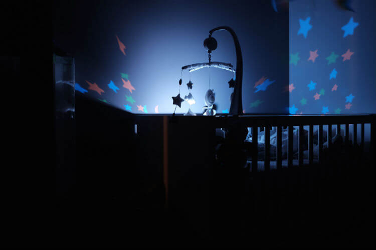 A dark baby room is illuminated by a starry night light