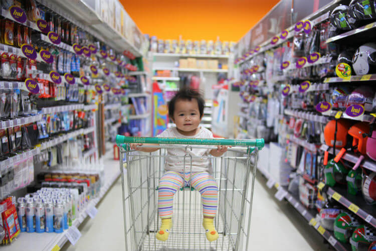 A baby sits in a shopping cart