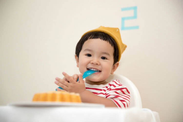 A smiling toddler eats with a plastic fork