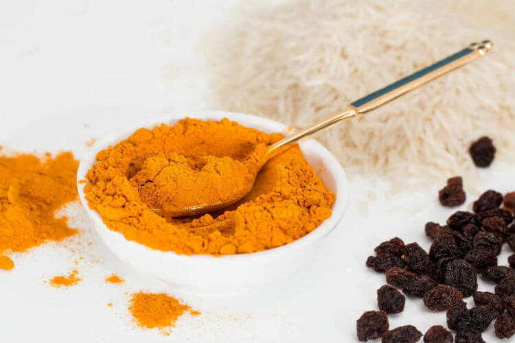 Spoon dipping into white bowl filled with turmeric powder