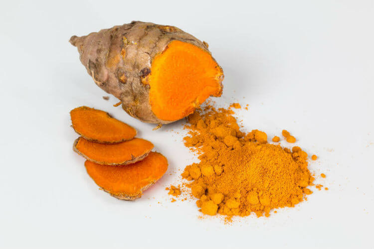 Turmeric root sliced up next to powder