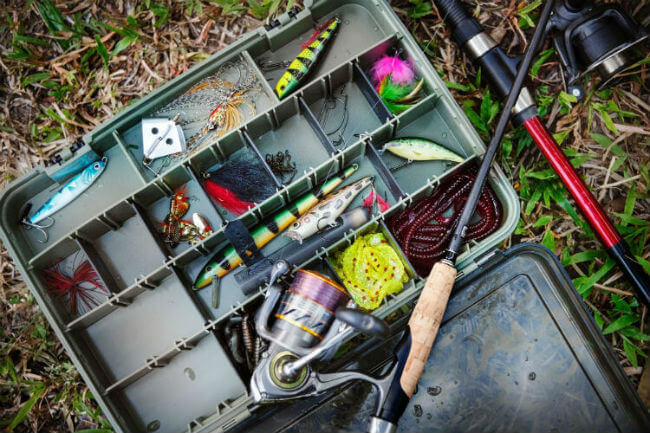 A tackle box filled with fishing gear on the grass next to some fishing poles