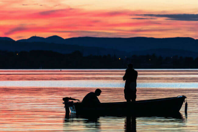 Two men sit in a boat at sunset