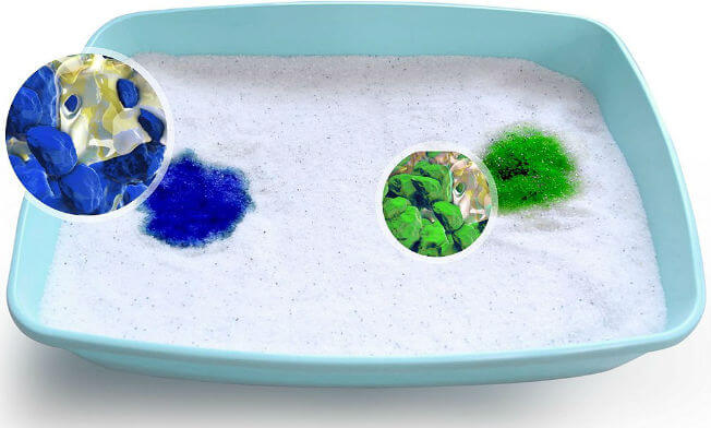 A litter box is filled with litter, with two spots colored green and blue