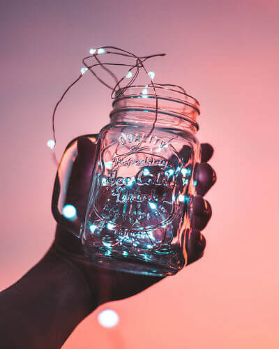A mason jar full of string lights is held against a pink sky