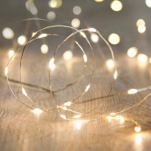 A bundle of white light string lights on a wooden surface