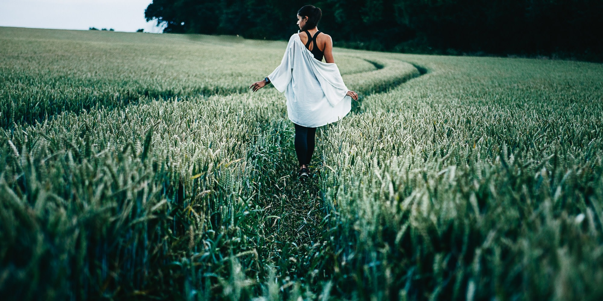 Woman walking through tall grass: metaphor for sustainable fashion