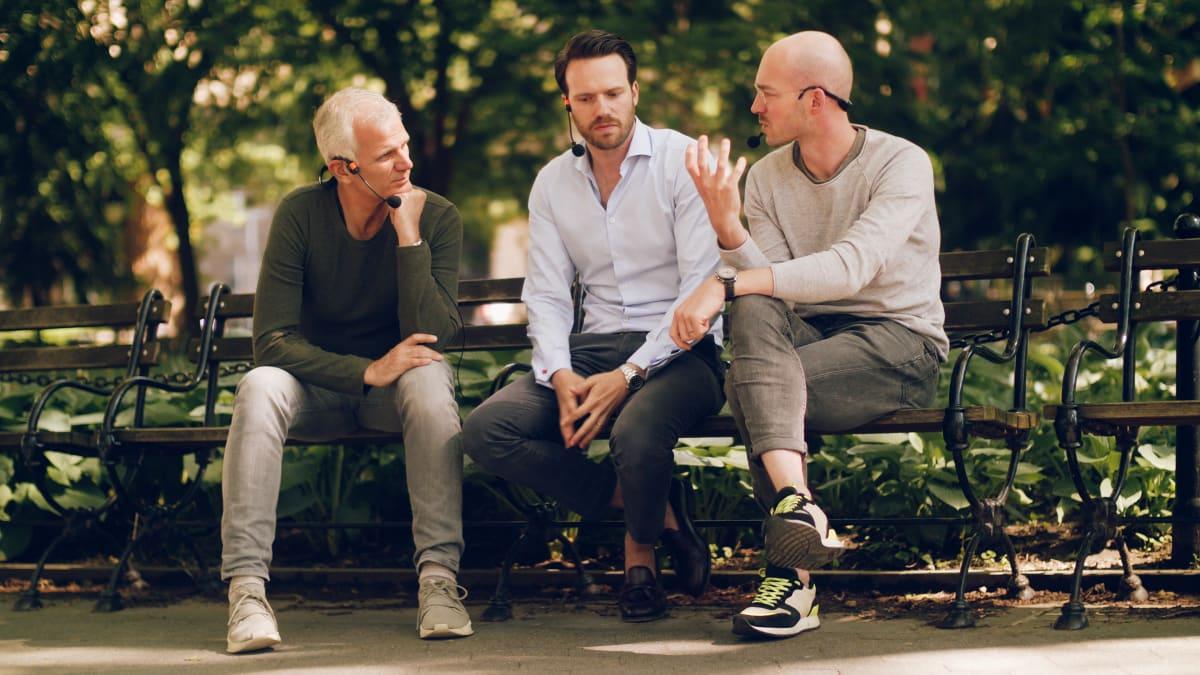 Drei Personen auf einer Bank, die miteinander sprechen