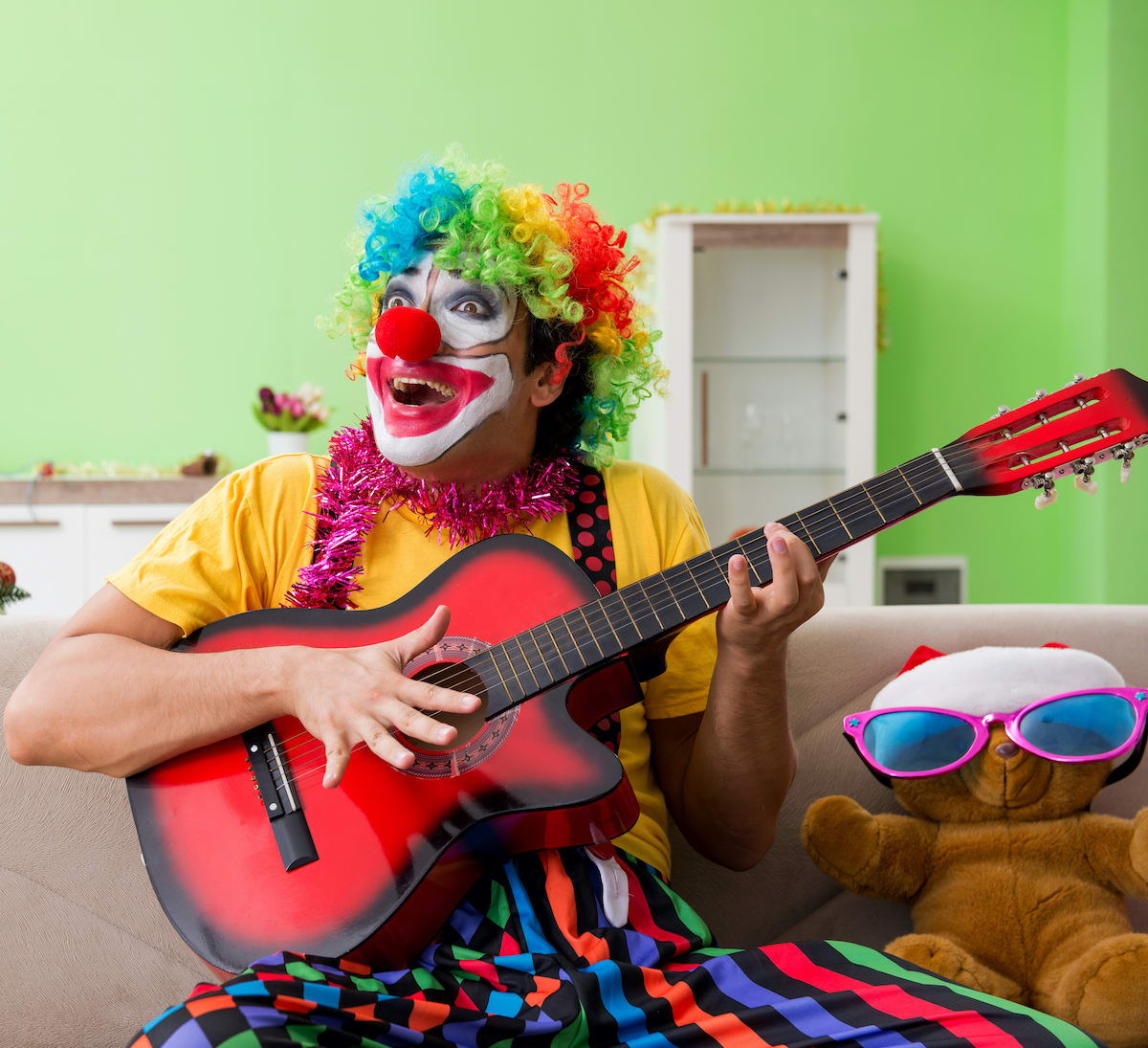 Clown plays the guitar and sings for our Flagstaff Singing Telegram Service