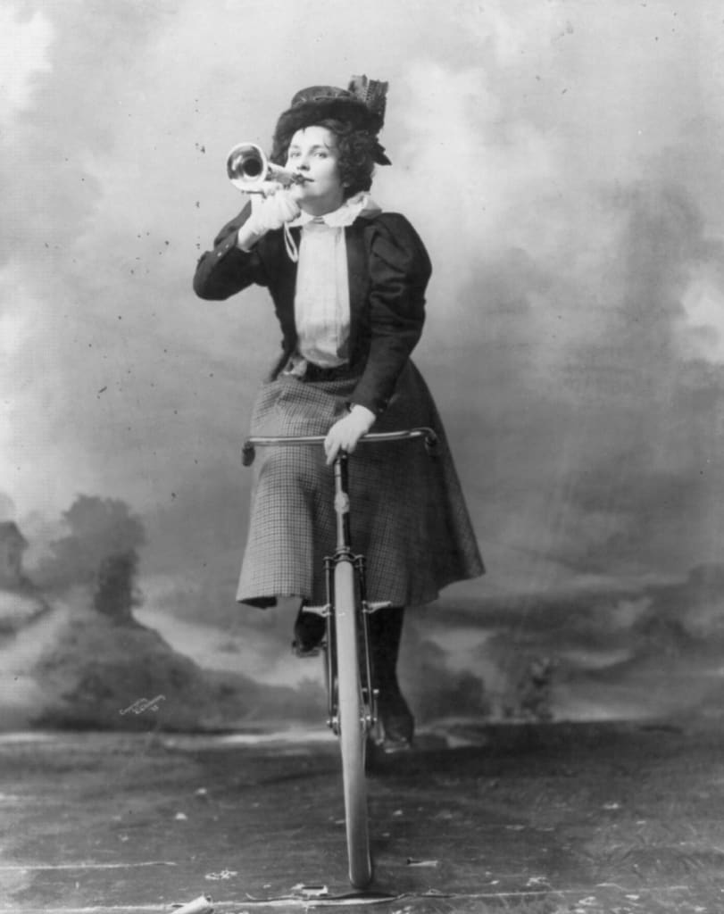 Black and white photo of woman on an old bike with a horn