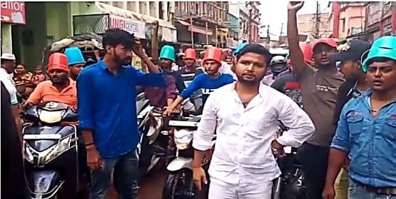 नये परिवहन कानून का राजद कार्यकर्ताओं ने किया अनोखा विरोध, बाल्टी पहनकर चलाया मोटरसाइकिल