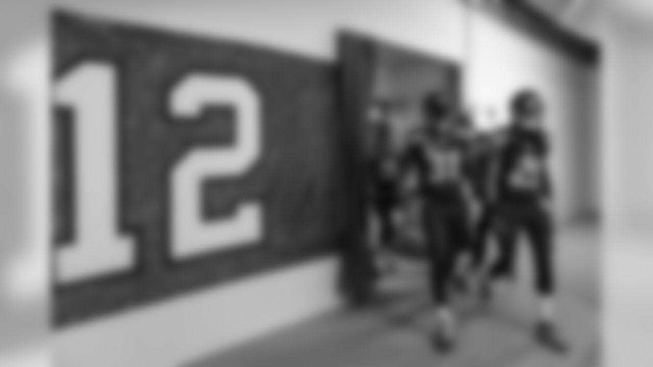 At 12:15, the defensive backs, led by Kam Chancellor and Richard Sherman, left the locker room an headed to the field, passing a large 12 flag signed by fans.