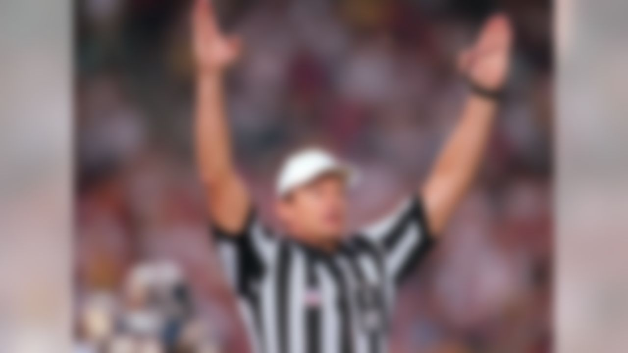 Referee Ed Hochuli signals a touchdown during an NFL football game between the San Francisco 49ers and San Diego Chargers on August 8, 1998, in San Diego. The Chargers won, 27-21.