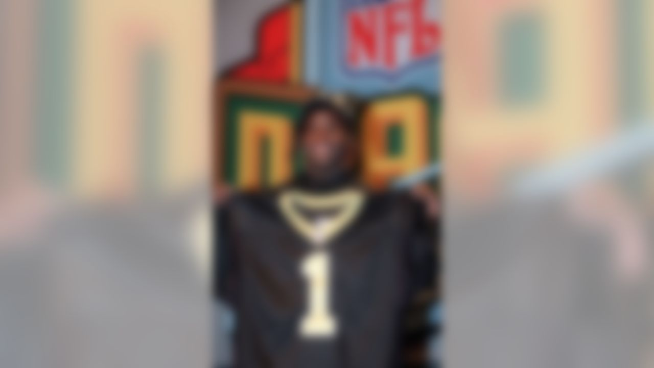 Texas running back Ricky Williams poses with a New Orleans Saints jersey after the Saints made Williams their first pick in the NFL draft and the fifth pick in the draft overall Saturday, April 17, 1999, in New York. Williams won the Heisman Trophy in 1998. (AP Photo/Suzanne Plunkett)
