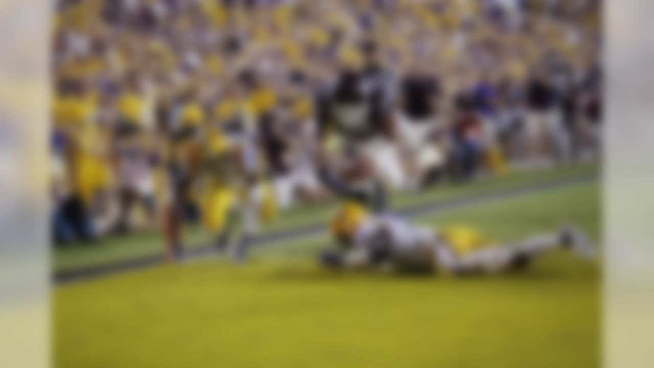 Mississippi State quarterback Dak Prescott (15) dives into the end zone over LSU cornerback Dwayne Thomas (13) and safety Ronald Martin (26) on a 56 yard touchdown carry in the second half of an NCAA college football game in Baton Rouge, La., Saturday, Sept. 20, 2014. (AP Photo/Gerald Herbert)