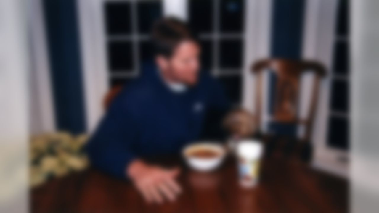 """Former NFL quarterback Brett Favre from the Minnesota Vikings eats breakfast with his dog """"Jaz"""" at his home in Green Bay Wisconsin in December of 1998."""